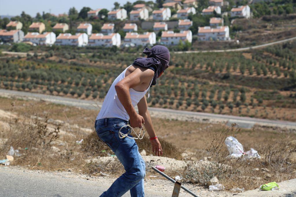 فلسطيني يتهيأ لرشق الجنود الإسرائيليين الذين يحمون مستوطنة حلميش بالحجارة، 28 اغسطس 2015 (Eric Cortellessa/Times of Israel)