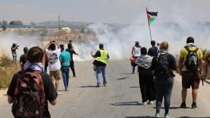المتظاهرون في النبي صالح في الضفة الغربية يواجهون الغاز المسيل للدموع بعد رشق الجنود الإسرائيليين بالحجارة، 28 اغسطس 2015 (Eric Cortellessa/Times of Israel)
