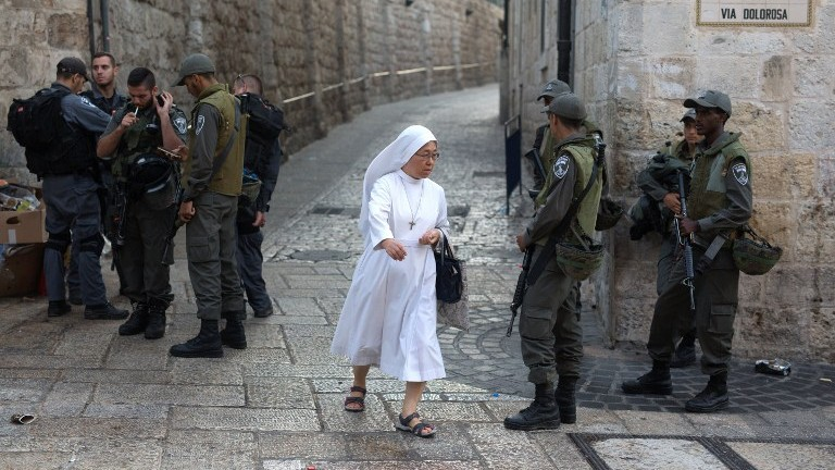 راهبة تمر امام عناصر شرطة اسرائيلية بينما يحرسون طريق الالانم في البلدة القديمة في القدس، 4 اكتوبر 2015 (AFP/MENAHEM KAHANA)