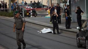 الشرطة بالقرب من جثمان منفذ هجوم طعن فلسطيني يبلغ 15 عاما في مكان وقوع الهجوم في حي بسغات زئيف شمال القدس، 12 اكتوبر 2015 (Yonatan Sindel/Flash90)