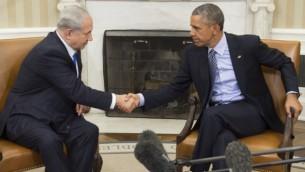 الرئيس الأمريكي باراك أوباما (من اليمين) ورئيس الوزراء بينيامين نتنياهو يتصافحان خلال إحتماع في المكتب البيضاوي في البيت الأبيض في العاصمة واشنطن، 9 نوفمبر، 2015. (AFP/Saul Loeb)