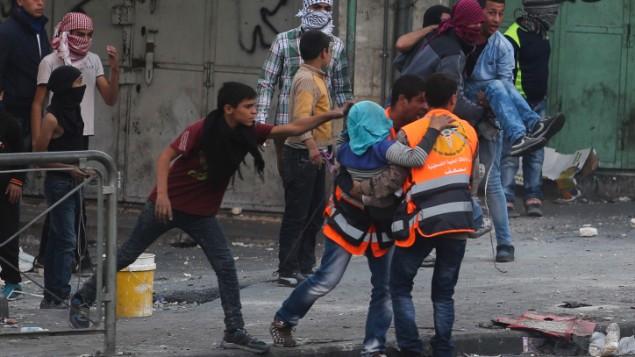 مسعفون فلسطينيون يحملون رجل مصاب خلال اشتباكات مع جنود اسرائيليين في الخليل، 31 اكتوبر 2015 (Flash90)