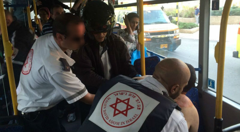 مسعفون يعالجون اسرائيلي يبلغ حوالي 40 عاما على متن حافلة في ريشون لتسيون بعد طعنه من قبل فلسطيني من الخليل، 2 نوفمبر 2015 (Eliran Avital/MDA)