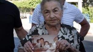 نينا كيرين، والدة داني حاران، وجدة عينات حارات، اللذان قتلا على يد سمير قنطار عند تسلله الى منزلهم في نهاريا عام 1982 واطلاق النار عليهما، تحمل صورة لابنها وحفيدتها، 15 يوليو 2008 (Kobi Gideon / FLASH90)