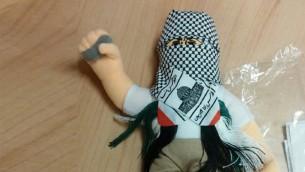 دمية ملثمة بكوفية وتحمل حجر صغير، عثر عليها في حاوية بطريقها الى السلطة الفلسطينية في مسناء حيفا، 8 ديسمبر 2015 (Haifa customs)