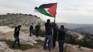 ناشطون فلسطينيون يرفعون العلم الفلسطيني في منطقة اي 1، شرقي القدس (Issam Rimawi/Flash90)