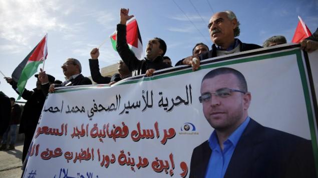 فلسطينيون يشاركون في تظاهرة بالقرب من رام الله للمطالبة بإطلاق سراح الصحافي الفلسطيني محمد القيق (الذي تظهر صورته على اللافتة) من سجن إسرائيلي، 22 يناير، 2016. (Abbas Momani/AFP)