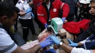 مسعفون يقدمون علاج طارئ لاحد ضحايا هجوم اطلاق نار على يد معتدي مجهول في تل ابيب، حيث قُتل شخصين واصيب 7، 1 يناير 2016 (AFP PHOTO/JACK GUEZ)