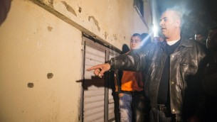 رجل يشير الى ثقوب الرصاص في موقع تبادل النيران بين نشأت ملحم وقوات الامن الإسرائيلية في بلدة عرعرة، 9 يناير 2016 (AFP PHOTO/JACK GUEZ)