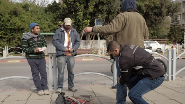 قوات الأمن الإسرائيلية تقوم بتفتيش جسدي لمواطنين عرب في إسرائيل بالقرب من محطة الحافلات المركزية في هرتسليا، خلال عمليات بحث عن مشتبهه في أعقاب تحذير بوقوع هجوم وشيك، 5 يناير، 2015. (Tomer Neuberg/Flash90)