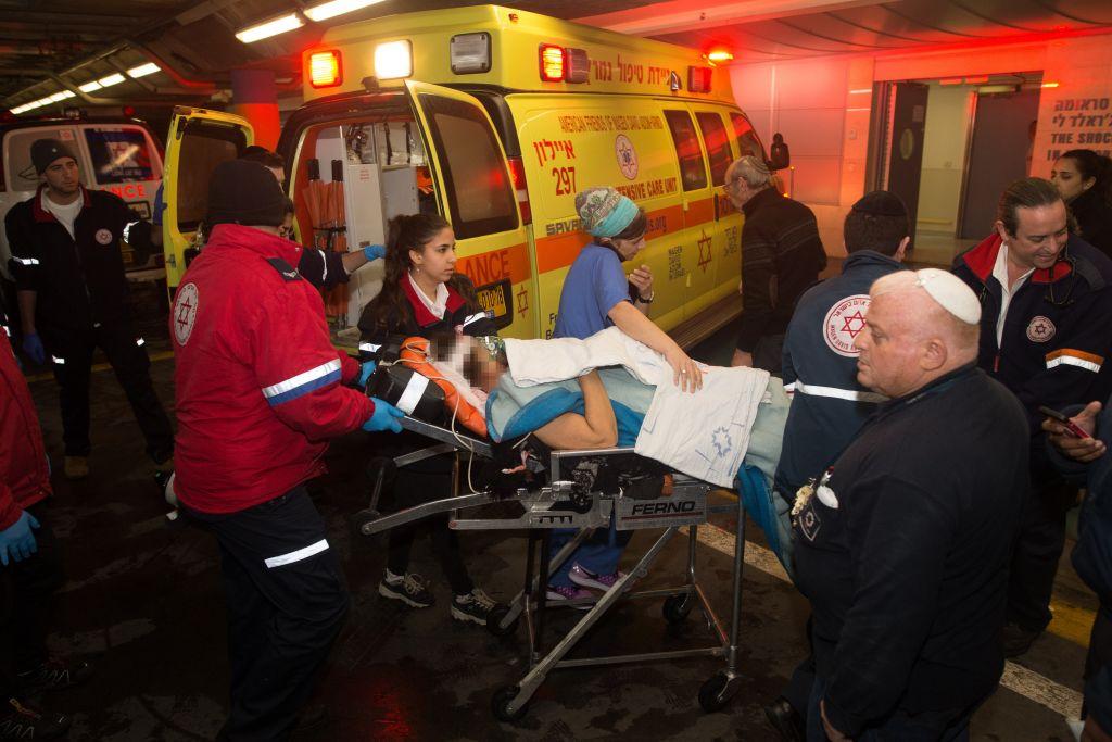 مسعفون ينقلون امرأة اسرائيلية اصيبت في هجوم طعن عند مدخل مستوطنة بيت حورن في الضفة الغربية الى غرفة الطوارئ في مستشفى شعاريه تسيديك، 25 يناير 2016 (Yonatan Sindel/Flash90)