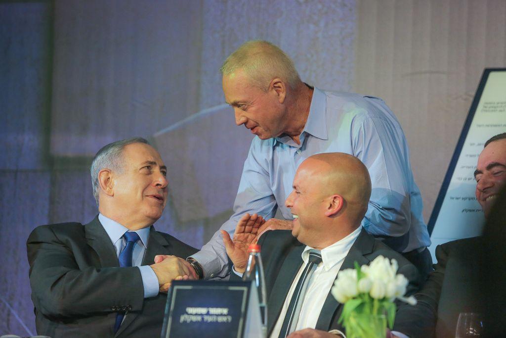 رئيس الوزراء بنيامين نتنياهو (يسار) ووزير الإسكان يؤاف غالانت (واقف) خلال حفل توقيع الاتفاق النهائي لبناء 32,000 وحدة سكنية جديدة في مدينة عسقلان الجنوبية، 29 اكتوبر 2015 (Edi Israel/Flash90)