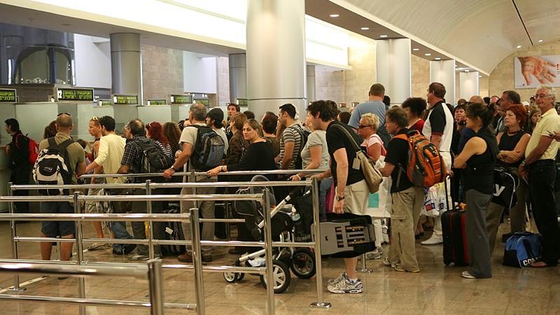 اشخاص يقفون بانتظار فحص جوازات السفر في مطار بن غوريون الدولي في اسرائيل (Yossi Zamir/Flash90)