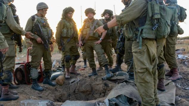 جنود إسرائيليون يقفون حول نفق في غزة في 24 يوليو، 2014. تم إستخدام الأنفاق كقنوات هجوم داخل إسرائيل وكوسيلة لقتال القوات الإسرائيلية داخل غزة. (Courtesy IDF Flickr)