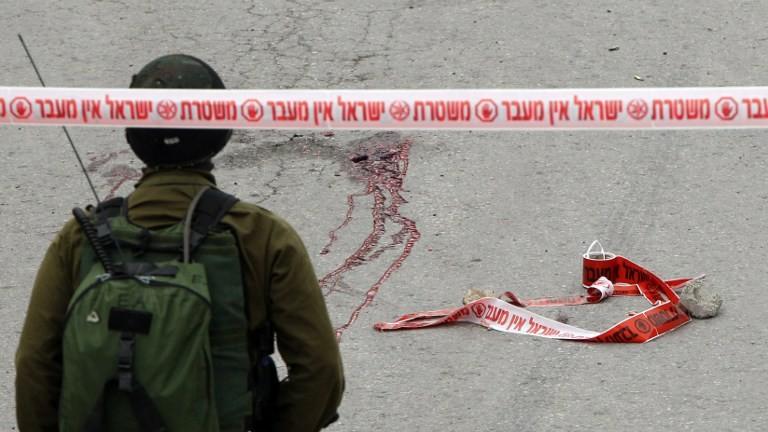 جندي إسرائيلي يقف امام شارع ملطخ بالدماء، بعد اطلاق النار على معتدي فلسطيني ملقى على الأرض في رأسه من قبل جندي في الخليل، 24 مارس 2016 (AFP/HAZEM BADER)