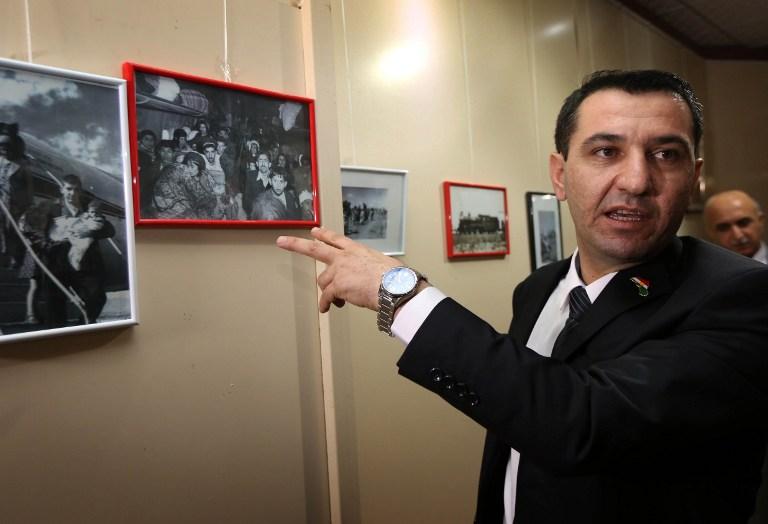 شيرزاد مامساني، ممثل اليهود في وزارة اقليم كردستان، يؤشر على صور معروضة خلال احياء ذكرى ترحيل اليهود من العراق قبل 7 عقود، في اربيل، عاصمة اقليم كردستان في شمال العراق، 30 نوفمبر 2015 (AFP/SAFIN HAMED)