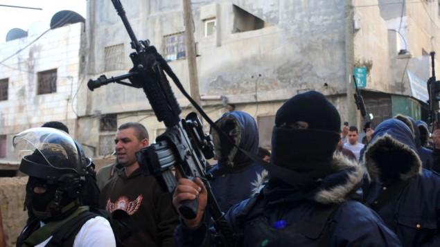 مسلحون فلسطينيون يسيرون خلال مظاهرة في مخيم قلنديا، 16 نوفمبر 2013 (Issam Rimawi/Flash90)