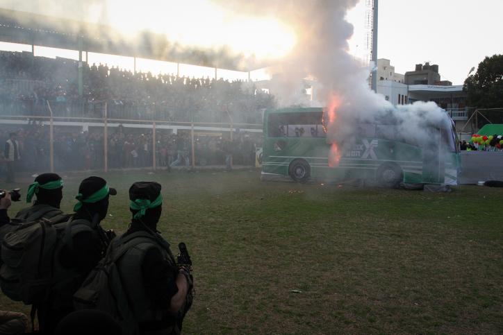 مقاتلون فلسطينيون من كتائب عز الدين القسام، الجناح العسكري لحركة حماس، يقومون بحرق مجسم حافلة إسرائيلية في مدينة رفج جنوبي قطاع غزة، 26 فبراير، 2016. (Abed Rahim Khatib/Flash90)