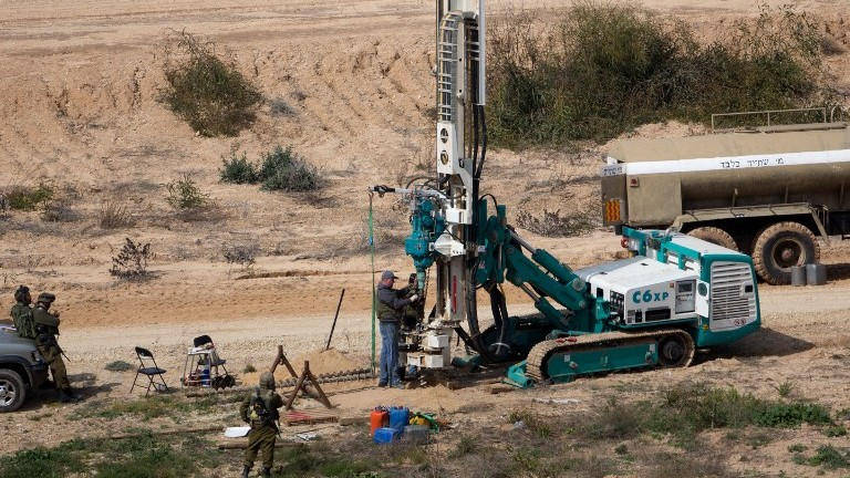 جنود اسرائيليون يحرسون بينما يتم الحفر في الارض على الطرف الإسرائيلي من الحدود مع قطاع غزة بحثا عن انفاق، 10 فبراير 2016 (AFP PHOTO/MENAHEM KAHANA)