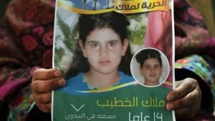 خولة الخطيب تحمل ملصق عليه صورة ابنتها، ملاك، البالغة 14 عاما، والتي حكمت عليها اسرائيل بالسجن شهرين لمحاولتها مهاجة جنود (AFP/Abbas Moman)