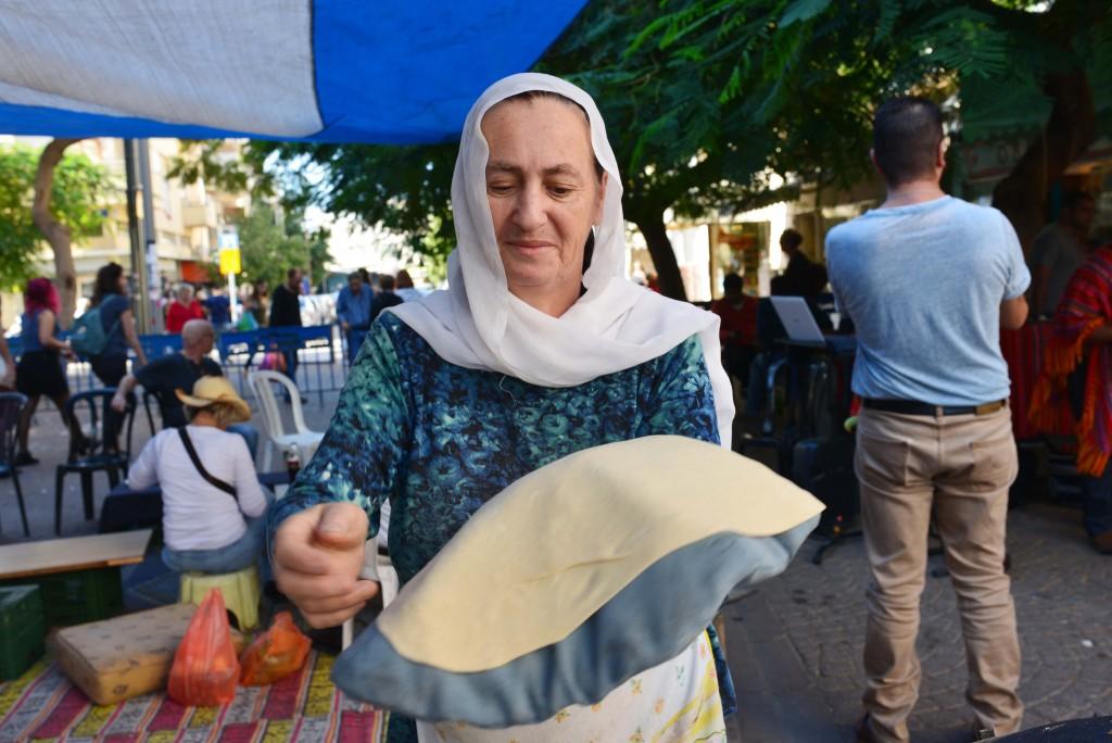 امرأة درزية تحضر خبز الصاج في سوق الكرمل في تل ابيب
