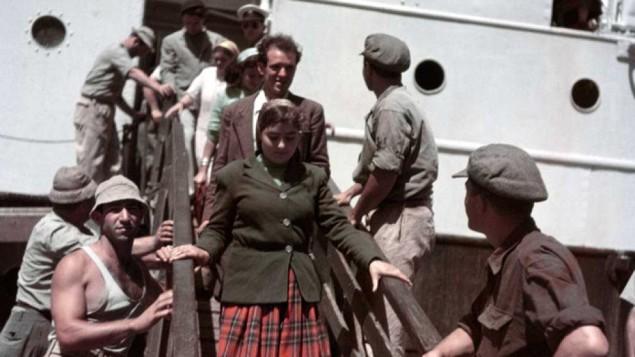 """مهاجرون جدد ينزلون من سفينة """"ثيودور هرتسل""""، بالقرب من حيفا، إسرائيل، 1949-1950 (Robert Capa/International Center of Photography/Magnum Photos)"""