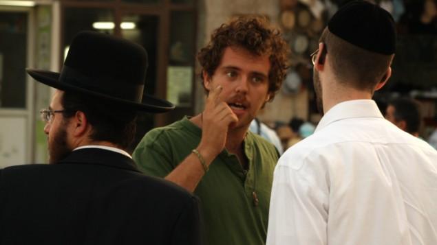 يهودي علماني يتحدث مع رجل حاريدي حول الخط الأخضر أمام بلدية القدس، 5 يونيو، 2013. (Lucie March/Flash 90)