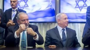 """رئيس الوزراء بينيامين نتنياهو، من اليمين، ورئيس حزب """"إسرائيل بيتنا"""" أفيغدور ليبرمان يوقعان على اتفاق لضم حزب ليبرمان إلى الحكومة، 25 مايو، 2016. (Yonatan Sindel/FLASH90)"""