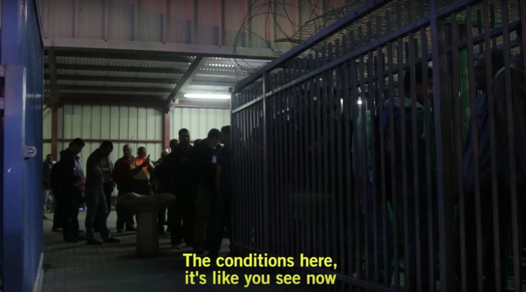 لقطة شاشة لعمال فلسطينيين في 3 مايو، 2016 في انتظار دخول ممر على شكل قفص حديدي يؤدي إلى المنطقة حيث يتم فحص بطاقات الهوية. (Luke Tress/Times of Israel)