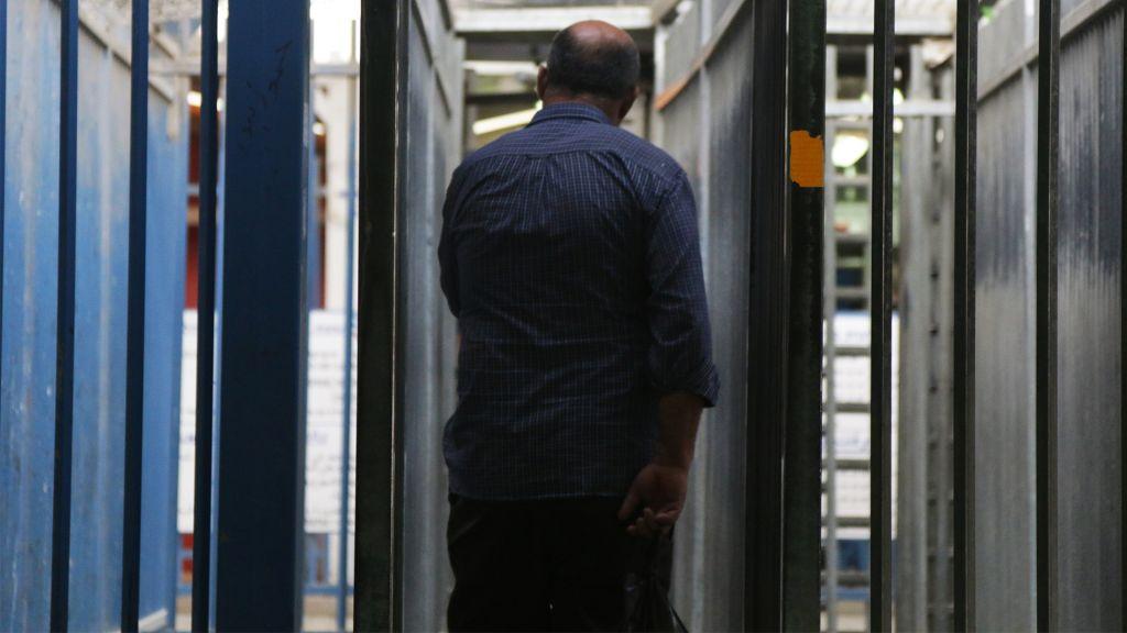 """صورة تم التقاطها في معبر قلنديا في 3 مايو، 2016، تظهر عاملا فلسطينيا يدخل """"الأكمام"""" الحديدية حيث يضطر الفلسطينيون العبور من خلالها قبل التحقق من بطاقات هوياتهم. (Luke Tress/Times of Israel)"""