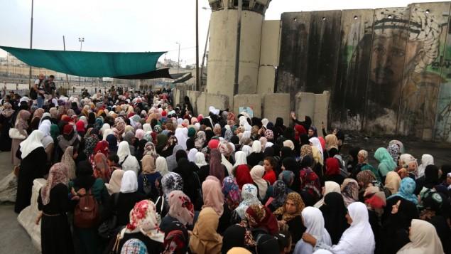 نساء فلسطينيان يحاولن عبور حاجز قلنديا في طريقهن إلى المسجد الأقصى للمشاركة في صلاة الجمعة، 26 يونيو، 2015. (Flash90)