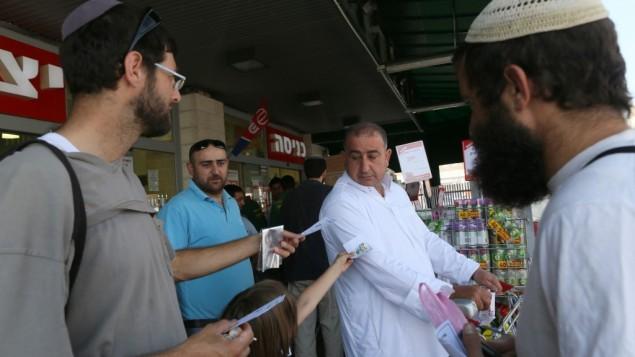نشطاء في منظمة 'إيرتس شالوم' يوزعون الحلوى على متسوقين عرب بمناسبة يوم الجمعة الأخير من شهر رمضان في سوبر ماركت 'رامي ليفي' في غوش عتصيون، 17 أغسطس، 2012. (Nati Shohat/Flash90)