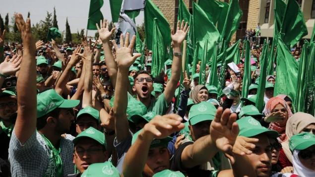 طلاب فلسطينيون مؤيدون لحركة حماس يشاركون في مسيرة إنتخابية للمجلس الطلابي في جاعمة بير زيت، بالقرب من مدينة رام الله في الضفة الغربية، 26 أبريل، 2016. (AFP/Abbas Momani)