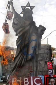 إشعال النار في تمثال يصور تمثال الحرية الأمريكي مزين بنجمة داوود على الرأس ويحمل صورا لرئيس الوزراء البريطاني السابق توني بلير ووزير الخارجية السعودي عادل الجبير على يد متظاهرين إيرانيين خلال مسيرة لإحياء 'يوم القدس' في طهران، 1 يوليو، 2016. ( / AFP PHOTO / ATTA KENARE)