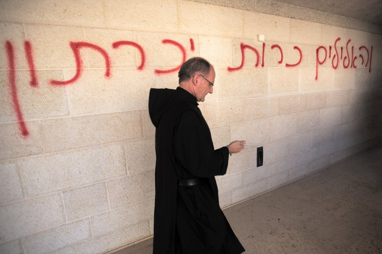 خوري يمشي امام عبارة 'سوف يتم تدمير الاوثان' باللغة العبرية، بينما يتفحص الاضرار الناجمة عن الحريق في كنيسة الطابغة على ضفاف بحيرة طبريا في اسرائيل، 18 يونيو 2015 (AFP/Menahem Kahana)