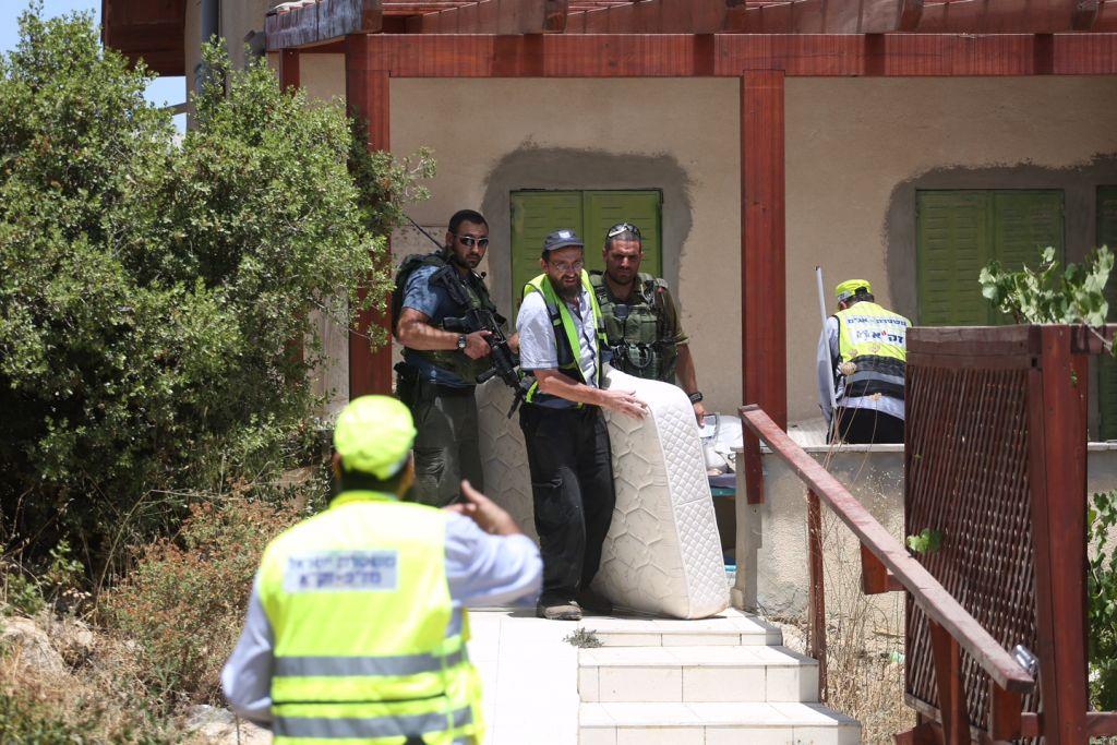 اول المستجيبين يخرجون فرشة من منزل هاليل يافا ارئيل (13 عاما) التي قُتلت طعنا بهجوم في مستوطنة كيريات اربع في الضفة الغربية، 30 يونيو 2016 (Hadas Parush/Flash90)