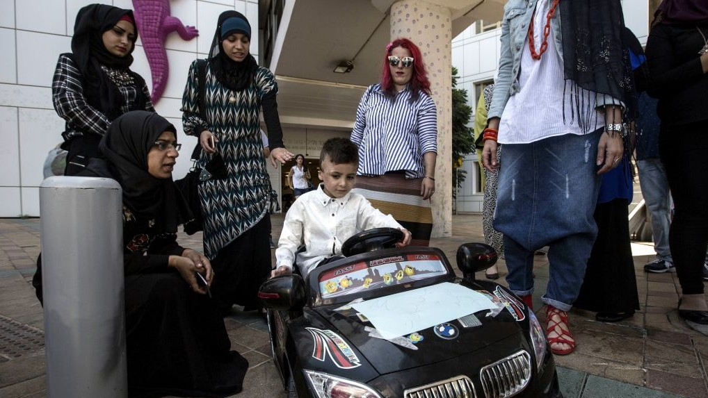 Palestinian relatives gather around Ahmed Dawabsha, the sole survivor of a West Bank arson attack in Duma village, as he rides a toy car at the Tel Hashomer Hospital, July 22, 2016. AP Photo/Tsafrir Abayov