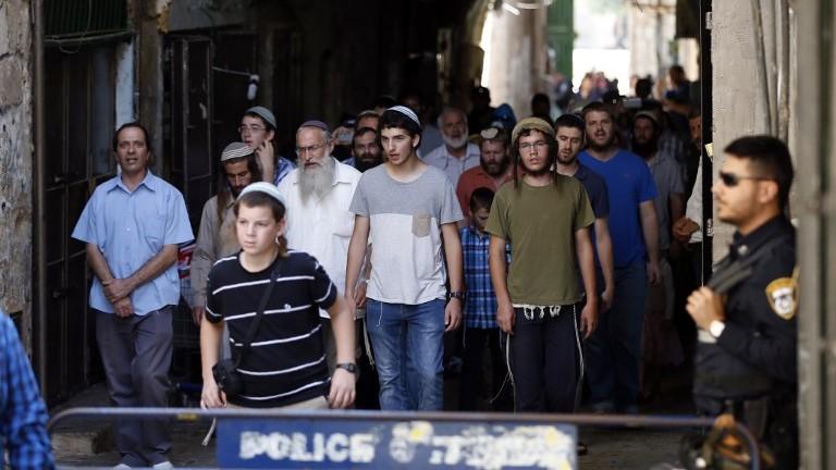 """قوات الامن الإسرائيلية تحرس بينما ينهي مجموعة شبان ورجال يهود زيارتهم الى الحرم القدسي-جبل الهيكل في القدس، في يوم """"التاسع من آب""""، 14 اغسطس 2016 (AFP PHOTO/AHMAD GHARABLI)"""