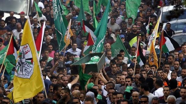 رجال فلسطينيون يحملون جثمان احمد قالي، الذي قُتل في اشتباكات مع القوات الإسرائيلية، خلال تشييع جثمانه في مخيم شعفاط في القدس الشرقية، 10 اكتوبر 2015 (Ahmad Gharabli/AFP)