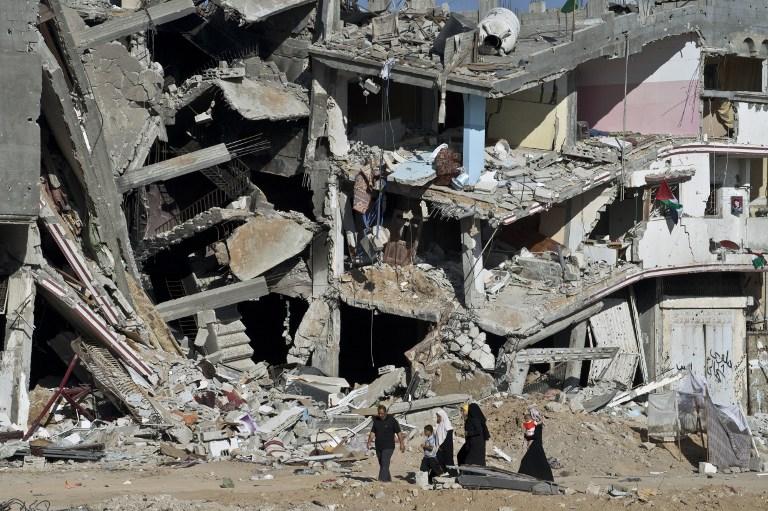 عائلة فلسطينية تمر امام مبنى منهار في حي الشجاعية في قطاع غزة، 27 اغسطس 2014 (AFP/ROBERTO SCHMIDT)