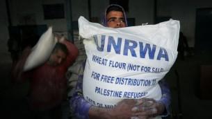 فلسطينيون يحصلون على مساعدات غذائية شهرية من مركز توزيع تابع للامم المتحدة في مخيم رفح، جنوب قطاع غزة، 8 فبراير 2015 (Abed Rahim Khatib/Flash90)