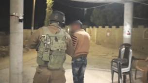 جنود اسرائيليون يعتقلون شقيق محمد طرايرة، المراهق الفلسطيني الذي قتل فتاة تبلغ 13 عاما طعنا في سريرها في مستوطنة كيريات اربع في شهر يونيو، خلال مداهمة في ساعات الصباح الباكر في بلدة بني نعيم في الضفة الغربية، 4 يوليو 2016 (Screen capture: IDF Spokesperson's Unit)
