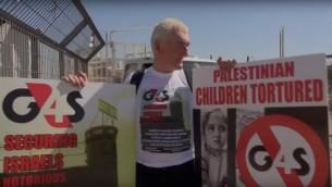 متظاهر يحمل لافتة ضد شركة G4S امام سجن عوفر الإسرائيلي، مايو 2013 (screen capture: YouTube)