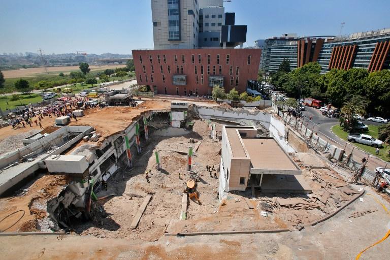 مسعفون ووحدات طوارئ يعملون في موقع بناء حيث انهار موقف سيارات تحت ارضي في حي رمات هحايال في تل ابيب، 5 سبتمبر 2016 (AFP PHOTO / GIL COHEN-MAGEN)