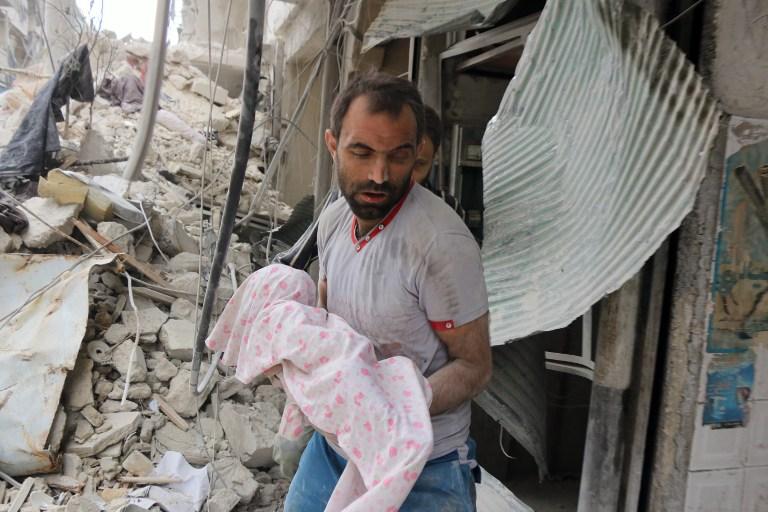 رجل سوري يحمل جثمان رضيع تم انتشاله من تحت الركام بعد غارة جوية في مدينة حلب السورية، 23 سبتمبر 2016 (AFP PHOTO/THAER MOHAMMED)