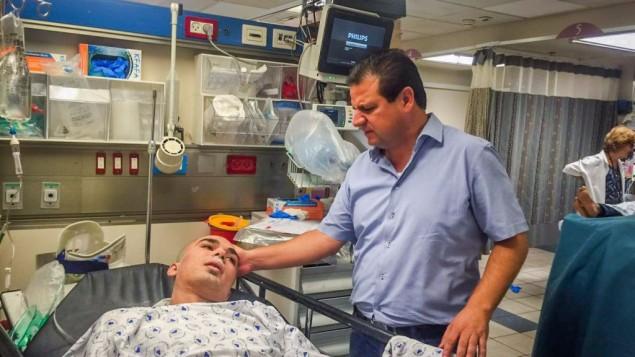 عضو الكنيست ايمن عودة يزور رجل اصيب في انهيار مبنى بتل ابيب، في مبنى ايخيلوف، 5 سبتمبر 2016 (Joint List)