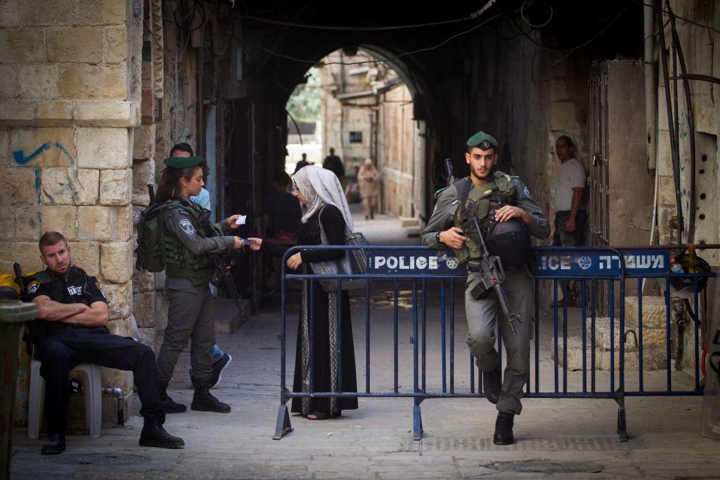 شرطية حدود اسرائيلية تفحص هوية امرأة مسلمة تغادر مسجد الاقصى في القدس القديمة، 17 سبتمبر 2015 (Miriam Alster/Flash90)