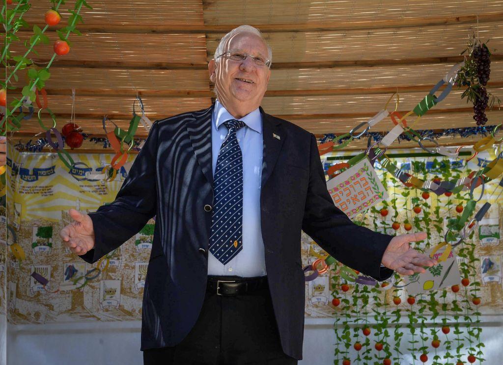 الرئيس رؤوفن ريفلين يزين 'سوكا' احتفالا بعيد ال'سوكوت' في منزل الرئيس في القدس، 13 اكتوبر 2016 (Mark Neyman/GPO)