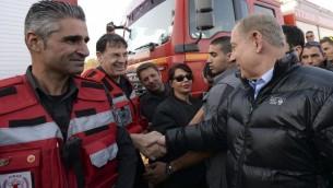 رئيس الوزراء بنيامين نتنياهو يتحدث مع رجال اطفاء اسرائيليين خلال زيارته لموقع قيادة للاطفاء في زخرون يعكوف، 23 نوفمبر 2016 (Haim Zach / GPO)