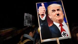 متظاهر يحمل لافتة عليها صورة الرئيس الامريكي المنتخب دونالد ترامب مع صليب معقوف وشارب يشبه شارب ادولف هيتلر خلال مظاهرة امام السفارة الامريكية في لندن، 9 نوفمبر 2016 (AFP PHOTO / BEN STANSALL)